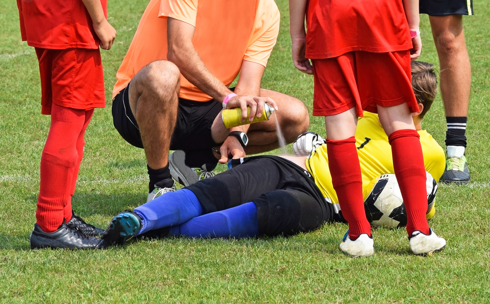 Injury on the soccer field, medic helps with a freezer spray